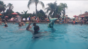 Mermaid Melissa makes a splash waving her mermaid tail to kids in the resort pool!